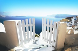 Open door in summer, vacation background. Oia village, Santorini, Greece, Europe location, famous and popular summer resort. White and blue color gamut photo, traditional Greek colors.