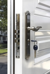 Open door of a family home. Close-up of the lock with your keys on an armored door.