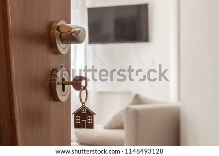 Open door to a new home. Door handle with key and home shaped keychain.   #1148493128