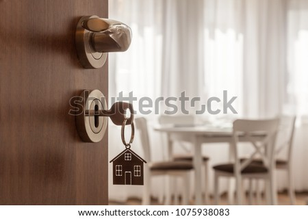 Open door to a new home. Door handle with key and home shaped keychain. Mortgage, investment, real estate, property and new home concept