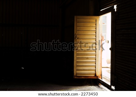 Open door to an industrial warehouse - shaft of light, High contrast