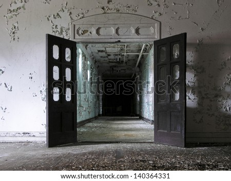 Open Doors Leading Into A Hallway Inside An Abandoned Mental Hospital.
