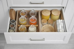Open drawer with different jars indoors. Order in kitchen