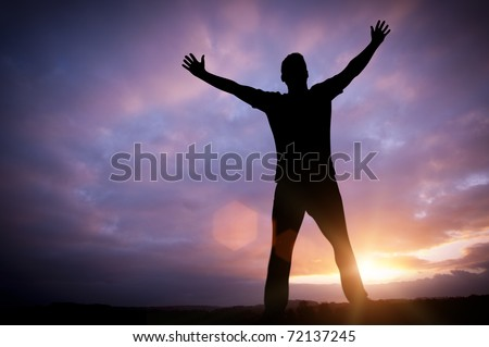 Open Dreams - A man standing with open arms set against a beautiful sunrise.