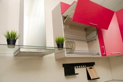 open drying cupboard with red facades next to a fume hood on which there are pots of artificial grass.