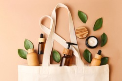 Open eco friendly cotton reusable bag with the different containers from the natural wood and brown glass.Fresh natural leafs around.Concept of organic,zero waste cosmetics.Woman bag with ac?essories.