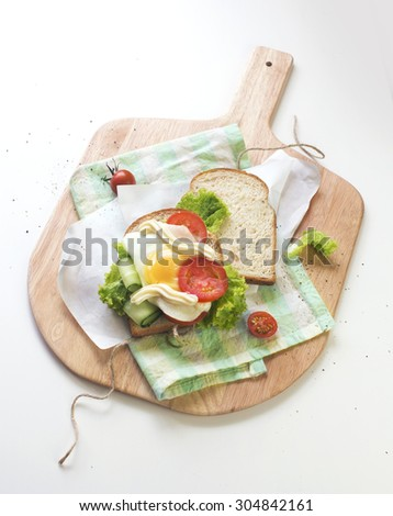 Open egg sandwich on wooden chop board with paper wrapper. White background. Table top view.