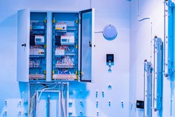 Open electrical cabinet at the enterprise. Utility room. Cabinet with electric wires and counters. Cabinet with electrical control devices in a factory. Room with electrical sensors.