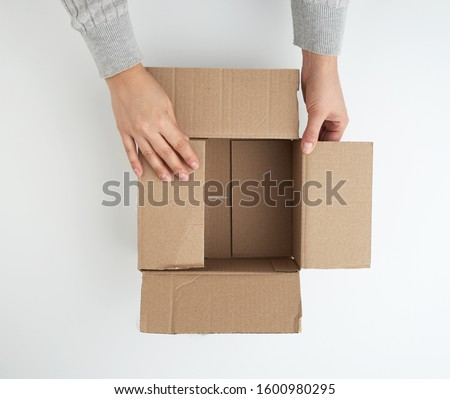 open empty square brown cardboard box for transportation and packaging of goods and two hands, view from the top