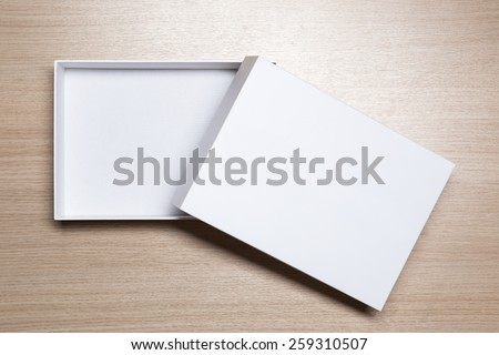 Open empty white box on wooden table