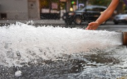 Open fire hydrant/child's hand touching water as it flows vigorously from opened fire hydrant in city street