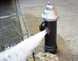 Open fire hydrant/water flowing vigorously from open fire hydrant on city street and sidewalk