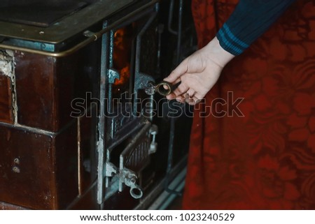 Open firebox with burning firewood, man's hand opens vintage metal door furnace. #1023240529