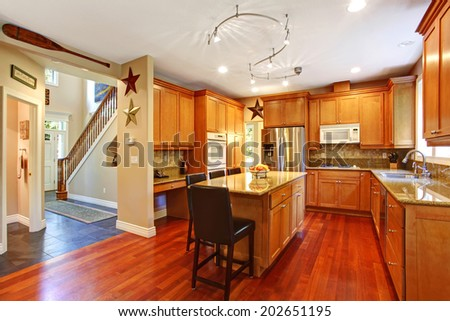 Open floor plan. View of elegant kitchen area with kitchen island. View of entrance hallway with stairs