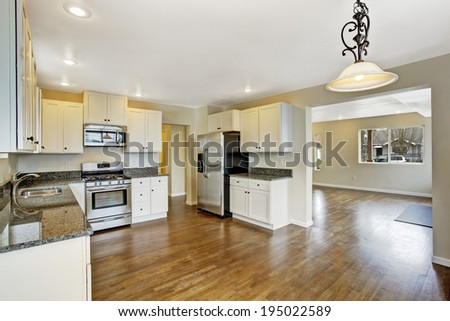 open floor plan white kitchen room with steel appliances view of empty living room stock photo. Black Bedroom Furniture Sets. Home Design Ideas