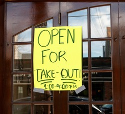 Open for take out only sign posted on the windows of a restaurant in Babylon Village New York USA because of the coronavirus COVID-19 pandemic.