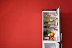 Open fridge full of food near color wall