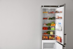 Open fridge full of food near white wall