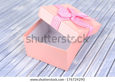 Open gift box on wooden background