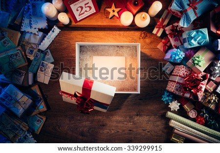 Open gift box with a blank white card inside, presents and Christmas letters all around, desktop top view