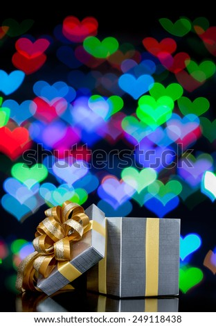 Open Gift box with Defocused bokeh lights in heart shaped background