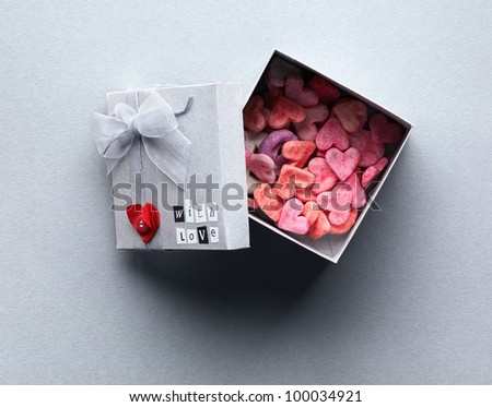 Open gift box with lots of cute little hearts inside. On gray textured paper background.