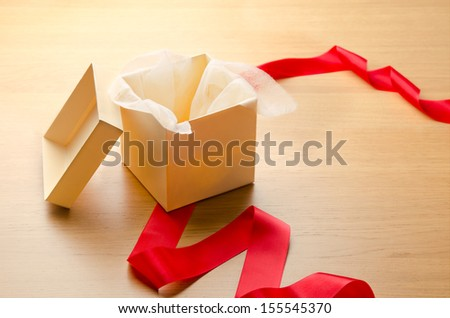 Open gift box with red ribbon