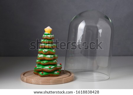 Open glas dome with gingerbread tree with sugar icing, sweet desert winter holiday cookies, artisan bakery
