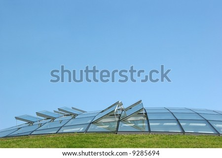 Open glass ventilation windows on a conservatory roof. Set against a blue sky with grass to the foreground. #9285694