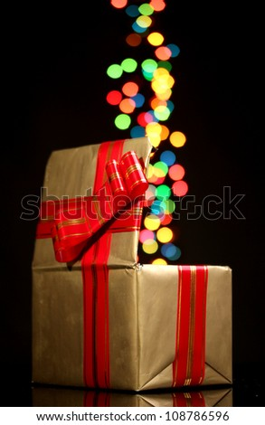 open golden gift box with bokeh background on black