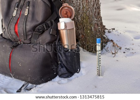 Open golden metal thermos with drink in photo camera backpack pocket on halt in winter hike under the tree trunk and Mercury thermometer in the snow showing negative temperature Celsius. Close up