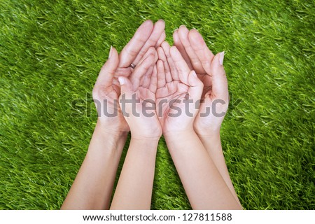 Open hand of mother and child outdoor on green grass