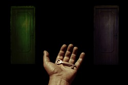 open hand with key in the palm in the foreground and two dark wooden doors in the background concept image
