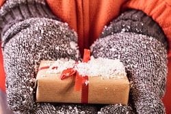 Open hands holding a present wrapped in a red ribbon