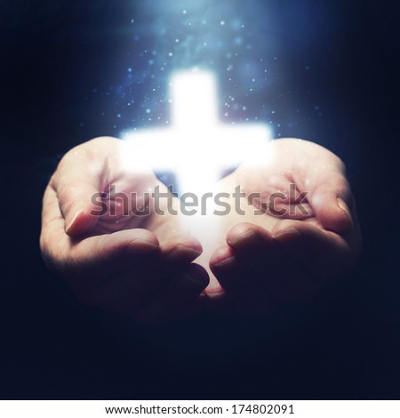Open hands holding cross, symbol of Christian faith. Religion and spirituality concept.