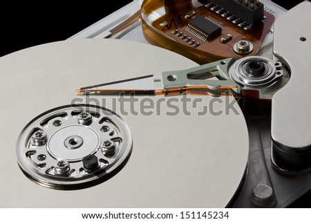 Open hard disk drive showing the read write arm and platter