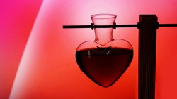 Open heart-shaped bottle of red love potion on a blurredred and pink background