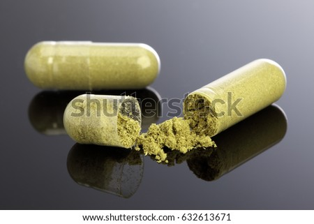 Open Herb Capsule on Black Background  #632613671