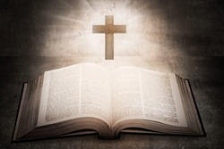 Open holy bible with wooden cross in the middle. Christian concept