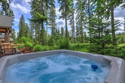 Open hot tub in the back yard with forest and golf course near luxury homes.