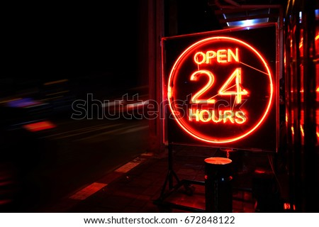 Open 24 Hours neon sign on the road side at night with moving cars.