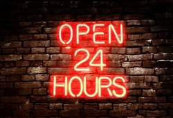 Open 24 Hours red neon sign on brick wall background