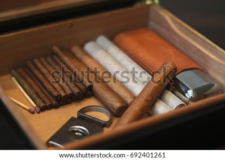 Open humidor with cigars and cigar cutter