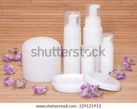 Open jar of cream and other body care cosmetics with flowers  on wooden background