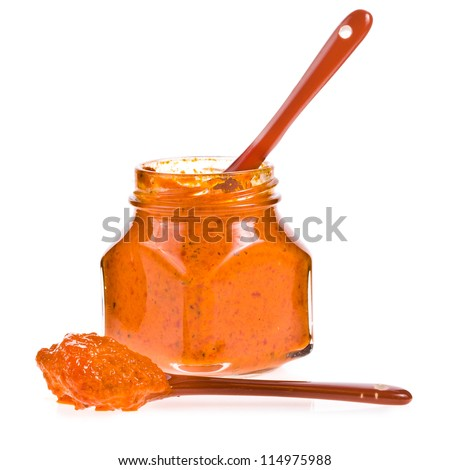 open jar of orange sauce from the pepper and ceramic spoons isolated on white background