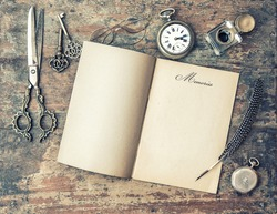 Open journal book and vintage writing tools. Feather pen, inkwell, keys on textured wooden background. Memories. Retro style toned picture.