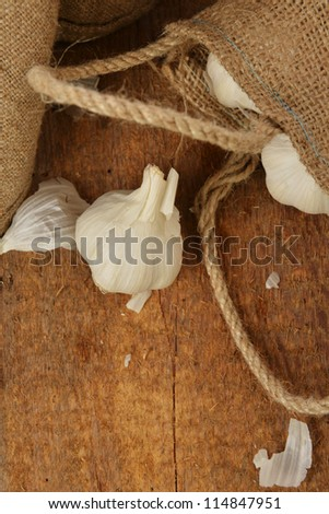 Open jute sack with ripe garlic  on wooden board