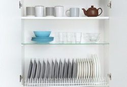 Open kitchen cabinet with different clean dishware