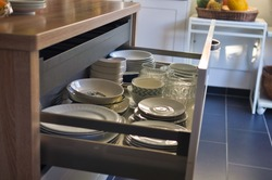 Open kitchen drawer plate organizer made of metal and wood connected to the kitchen island; plates and bowls  arrangement