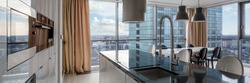 Open kitchen with black countertop, white cupboards and big windows and city view